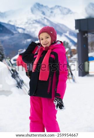 Cute smiling girl throwing snowball at highland resort - stock photo