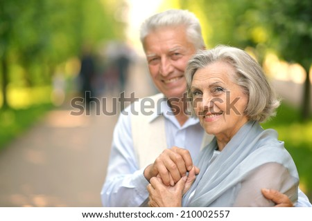 Cute smiling happy mature couple posing outdoors - stock photo