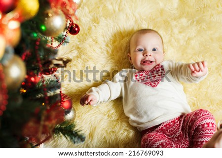cute smiling infant boy lies on the fur near the Christmas tree - stock photo