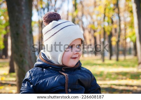 Cute smiling kid outdoors in autumn - stock photo
