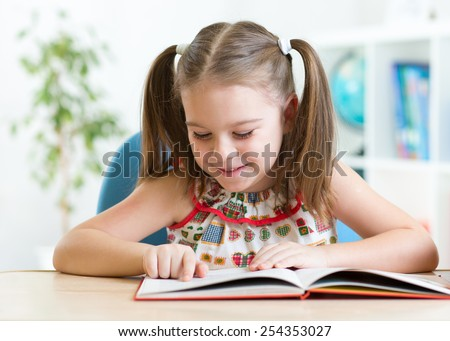 cute smiling kid reading book in children room - stock photo