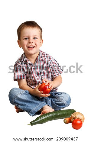 Cute smiling little boy with healthy vegetables and fruits from the garden - stock photo