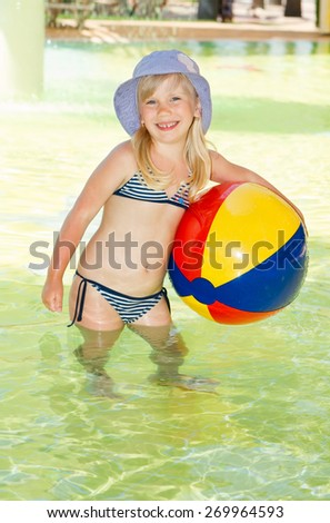 Cute smiling little girl hold ball in the swimming pool - stock photo