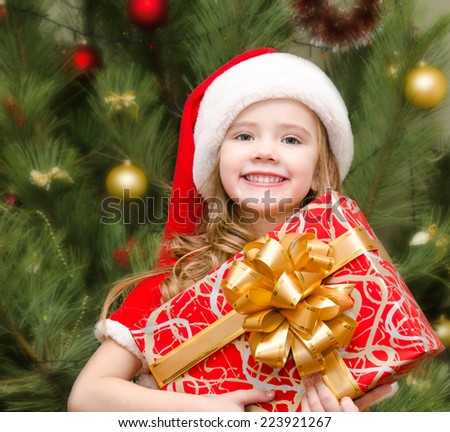 Cute smiling little girl in santa hat with gift box near christmas tree - stock photo