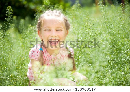 Cute smiling little girl  on the meadow in sunny day - stock photo