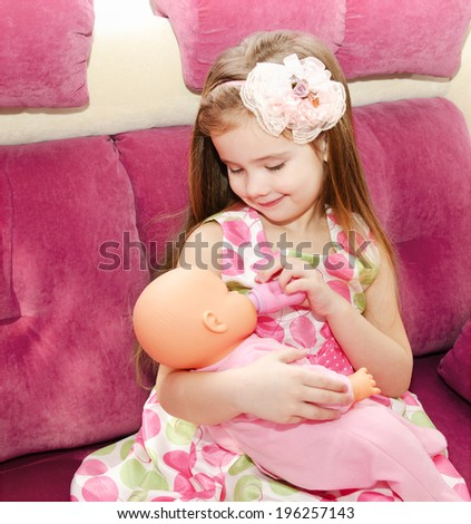 Cute smiling little girl playing with a doll at home - stock photo