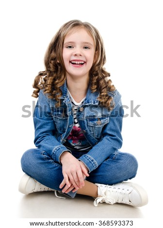 Cute smiling little girl sitting on the floor isolated on a white - stock photo