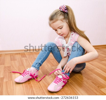 Cute smiling little girl tying her shoes at home - stock photo