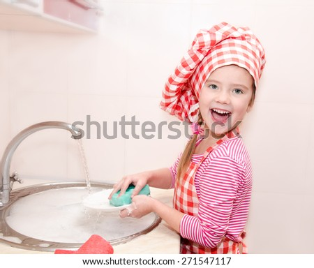 Cute smiling little girl washing the dishes in the kitchen - stock photo