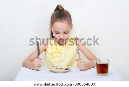 Cute smiling little girl with angry or sad expression sitting by dinner table and eating. Kid eats healthy food. Fine dinning. - stock photo
