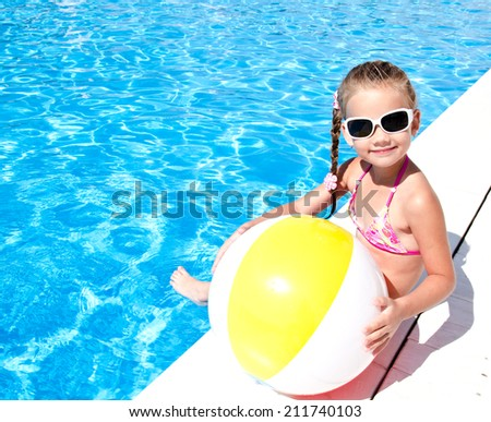 Cute smiling little girl with ball in swimming pool  - stock photo