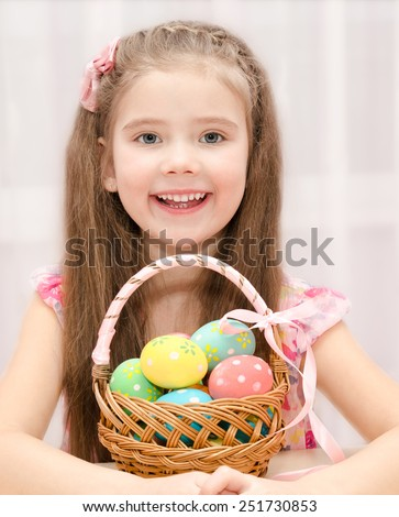 Cute smiling little girl with basket full of colorful easter eggs  - stock photo