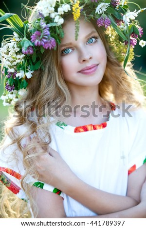 Cute smiling little girl with flower wreath on the meadow at the farm. Portrait of adorable small kid outdoors. Midsummer. Earth Day - stock photo