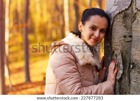 Cute smiling woman posing near tree in forest while autumn season - stock photo