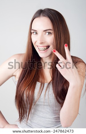 cute smiling woman with braces showing two fingers  - stock photo