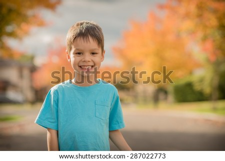 Cute smiling 5 year old mixed race Asian Caucasian boy stands in the street of his suburban neighborhood with beautiful Autumn (Fall) trees lining the street - stock photo