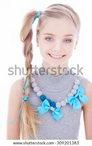 Cute smiling young girl with long blond hair in grey dress. - stock photo