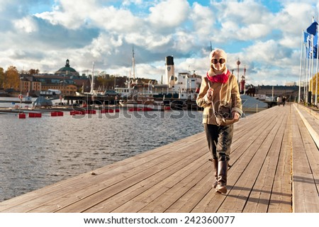 Cute smiling young stylish and trendy girl walking on pier in Stockholm on cloudy sky background. Autumn outdoors. - stock photo