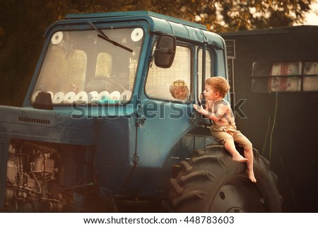 Cute smudgy little boy without t-shirt and shoes, and in pants with suspenders sitting on the tractor and looking inside dreaming to be a tractor-driver. Image with selective focus and toning - stock photo