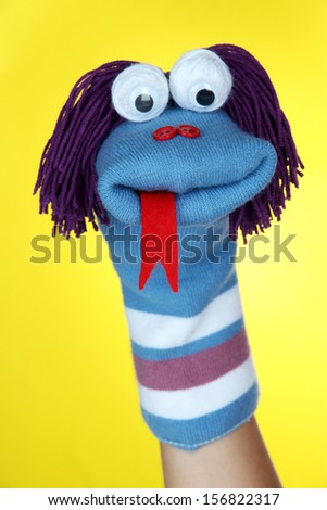 Cute sock puppet on yellow background - stock photo