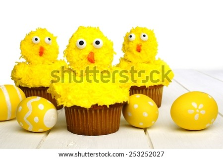 Cute spring chick cupcakes on white wood with Easter eggs - stock photo