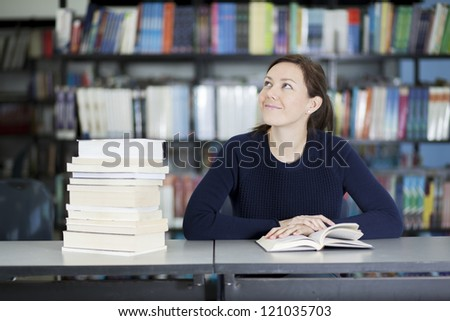 Cute student doing some reading at the library - stock photo