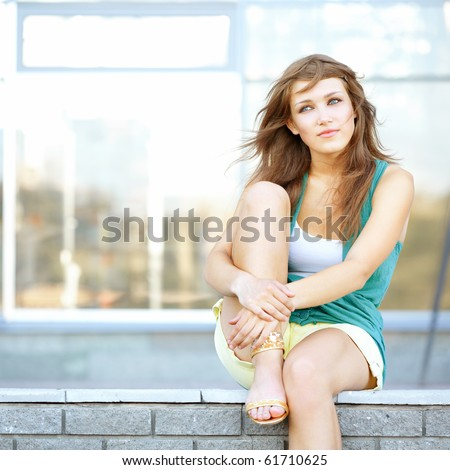 Cute student teenage girl sitting at urban scene. She is dreaming about something. - stock photo