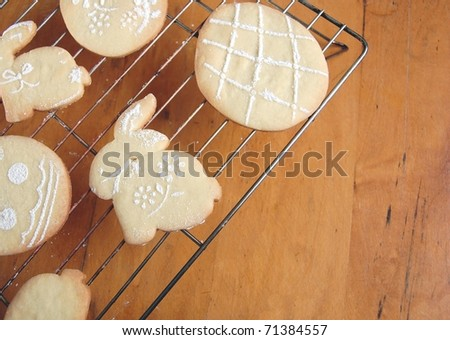 Cute, Sugar Powdered Easter Cookies Cooling on a Rack on a Wooden Table, with Room for Text - stock photo