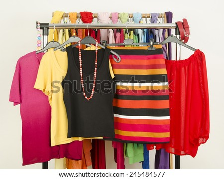 Cute summer outfits displayed on a rack. Wardrobe with colorful summer clothes and accessories. Striped skirt with matching blouses. - stock photo