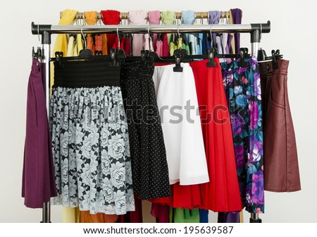 Cute summer skirts displayed on a rack. Wardrobe with colorful summer clothes and accessories. - stock photo