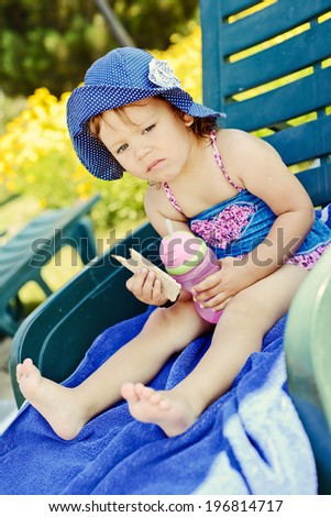 cute summer toddler eating on the sun lounger - stock photo