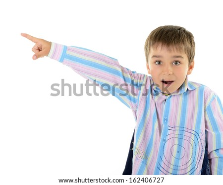 Cute surprise little boy pointing at copyspace, over white background - stock photo