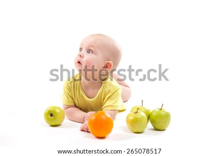 cute surprised baby looks at green apple on a white background, with depth of field photo - stock photo