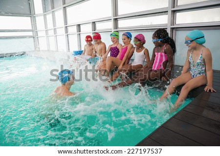 Cute swimming class in pool with coach at the leisure center - stock photo
