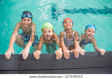 Cute swimming class in the pool at the leisure center - stock photo