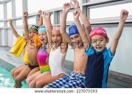 Cute swimming class smiling poolside at the leisure center - stock photo