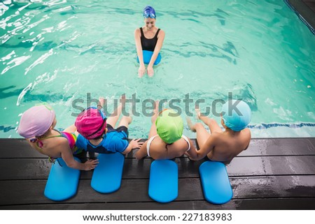 Cute swimming class watching the coach at the leisure center - stock photo