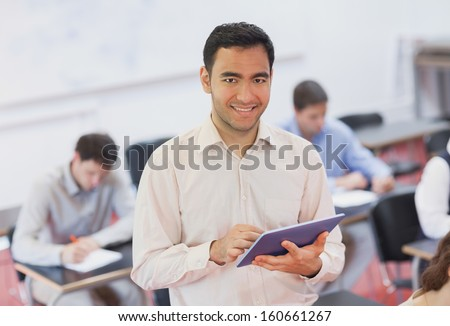 Cute teacher holding his tablet while posing in his classroom and smiling at camera - stock photo