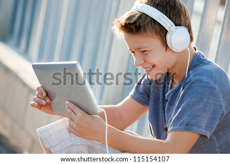 Cute teen boy listening to music with headphones and tablet outside. - stock photo