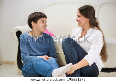Cute teen boy with his young mother at home - stock photo