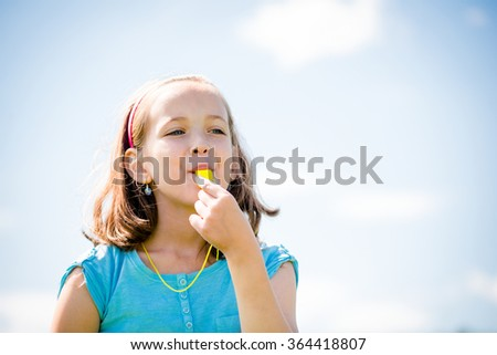 Cute teen girl blowing in whistle - blue sky in background - stock photo
