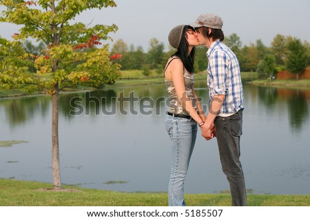 cute teen guy and girl kissing by a lake - stock photo