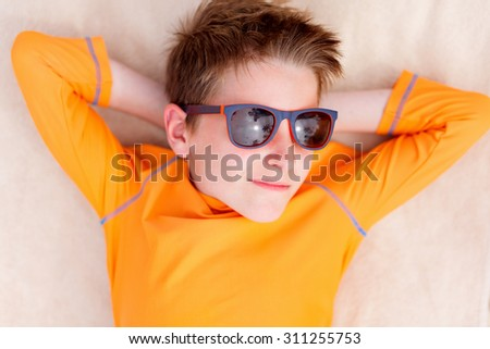 Cute teenage boy lying on a beach towel during summer vacation - stock photo