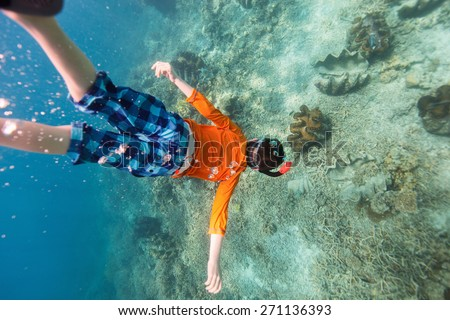 Cute teenage boy swimming underwater in a clear tropical water at coral reef with giant clams - stock photo