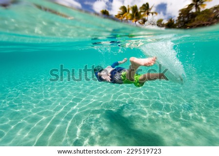 Cute teenage boy swimming underwater in shallow turquoise water at tropical beach - stock photo