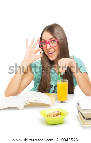 Cute teenage girl feeling happy gesturing okay while learning for school and drinking orange juice. Isolated on white background. Beautiful young woman reading a book wearing pink eyeglasses. - stock photo