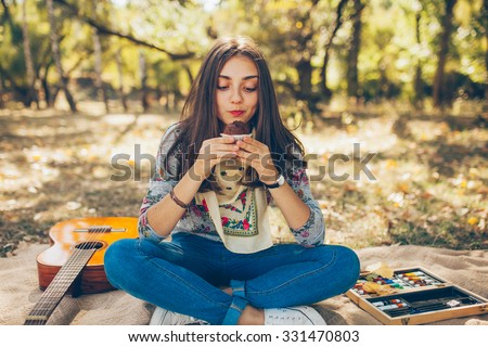 Cute teenage girl hipster looking at brownie cupcake outside on autumn day. Artsy young woman with guitar having a picninc in forest - stock photo