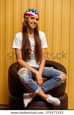 Cute teenage girl in a t-shirt, jeans and a bandana looking in camera and smiling while sitting on tires against orange background - stock photo