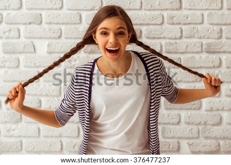 Cute teenage girl in casual clothes playing with her braids, looking in camera and smiling, standing against white brick wall - stock photo