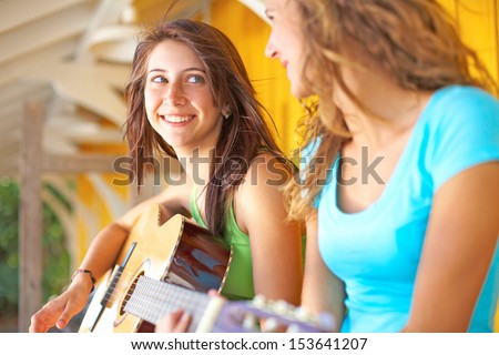Cute teenage girl looking at her female friend while playing guitar. Horizontal shot. - stock photo